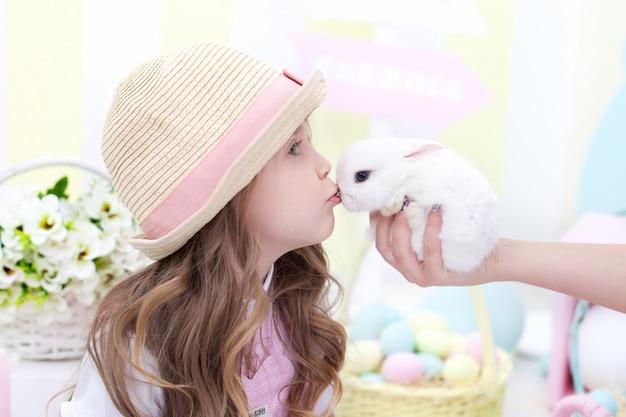 イースター!かわいい女の子はウサギにキスします。イースターのカラフルな装飾。子供はふわふわのウサギと遊ぶ。動物への愛。農業。子供と庭。小さな農家。田舎の動物。アレルギー。春の花 Premium写真