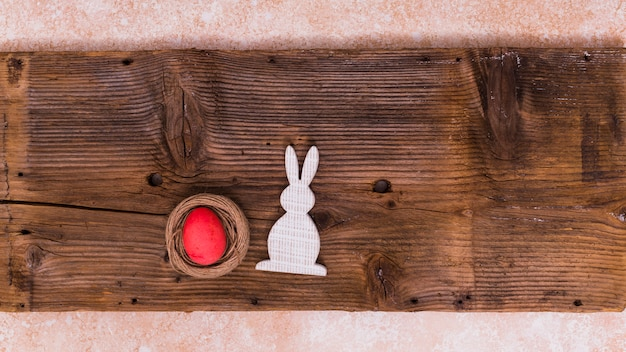 Easter egg in nest with rabbit on table Premium Photo