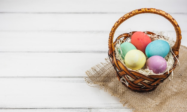 Easter eggs in basket on wooden table Free Photo