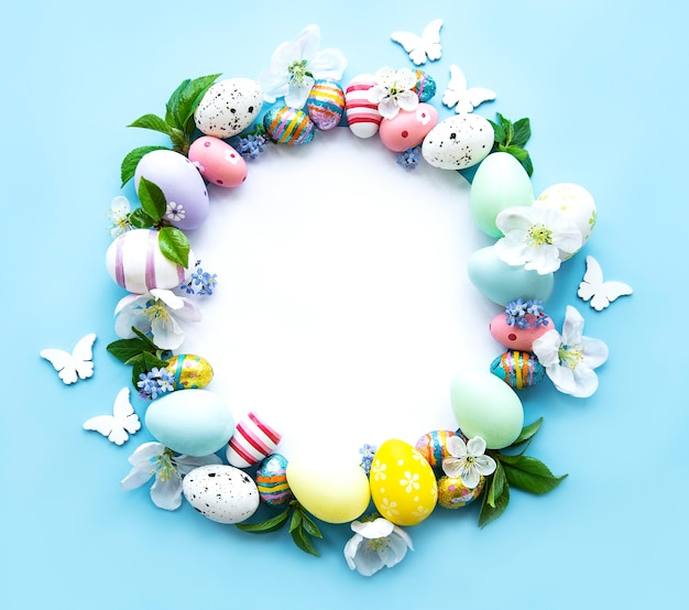 부활절 달걀, 파스텔 블루 테이블에 화려한 꽃. 봄, 부활절 개념입니다. 평면 위치, 평면도, 복사 공간, 원 프리미엄 사진