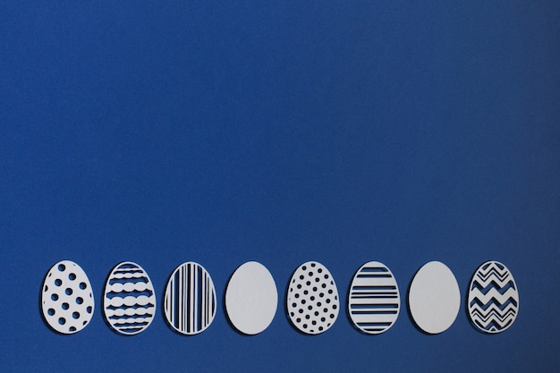 Easter eggs cut from paper on a classic blue background, color 2020 classic blue pantone Premium Photo