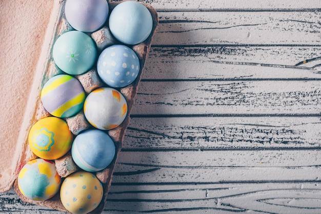 軽い木製の背景に卵のカートンのイースターエッグ。 無料写真