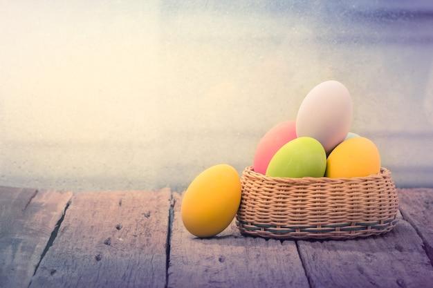Пасхальные яйца в гнезде на деревенской деревянной доске Premium Фотографии