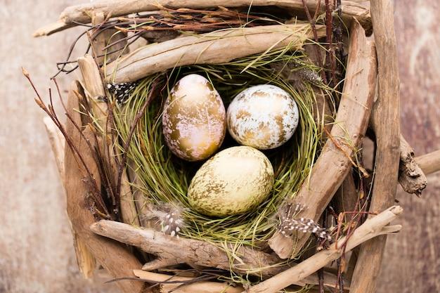 素朴な木製のテーブルに巣のイースターエッグ Premium写真