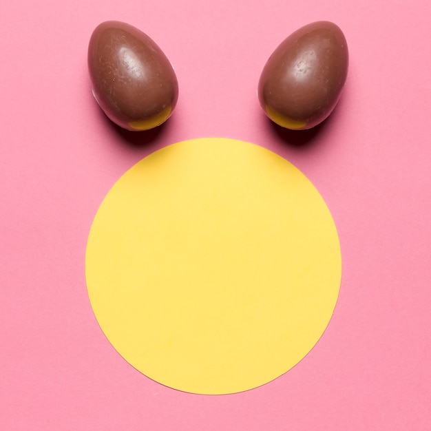 Easter eggs like bunny ear's over the round paper blank frame against pink backdrop Free Photo