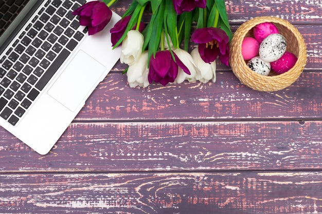 Easter eggs, mockup laptop and bouquet of tulips. Premium Photo