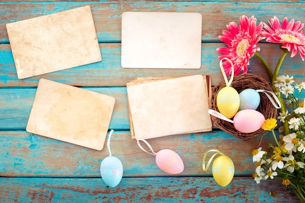 Easter eggs in nest with flower and empty old paper photo album on wood table Premium Photo