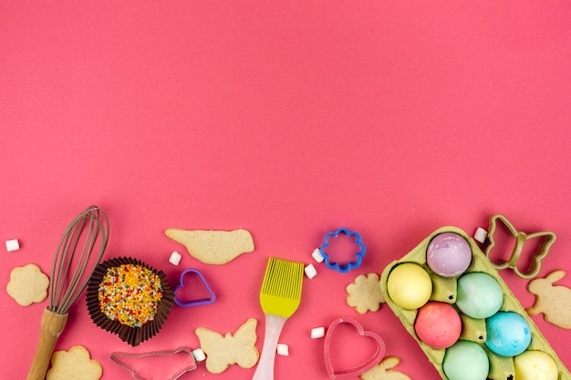 Easter eggs in rack with cookies and kitchen utensils Free Photo
