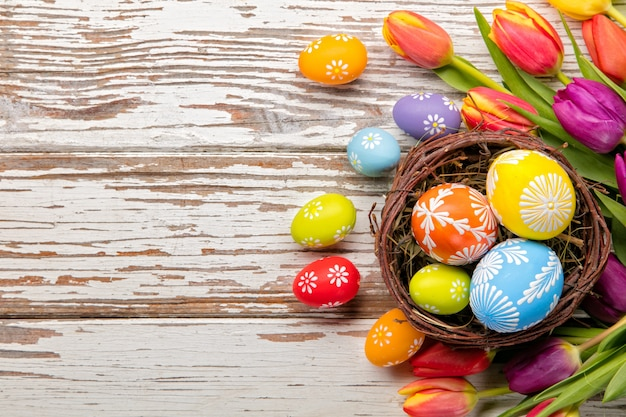 Easter eggs and tulips on wooden planks Premium Photo