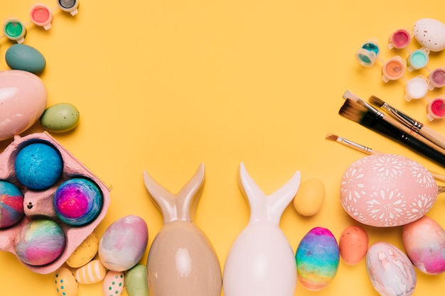 Easter eggs with bunny ears and paint brushes with space for writing the text Free Photo