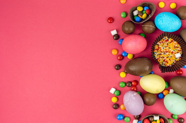 Easter eggs with chocolate eggs and candies on table Free Photo