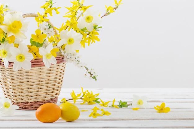 Пасхальные яйца с весенними цветами на белом деревянном столе Premium Фотографии