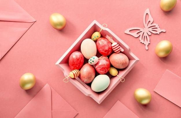 イースターフラットは、装飾的な卵、グリーティングカード、封筒、装飾的なフローズがいっぱいの木製トレイのあるサンゴ色の紙の上に置いた Premium写真