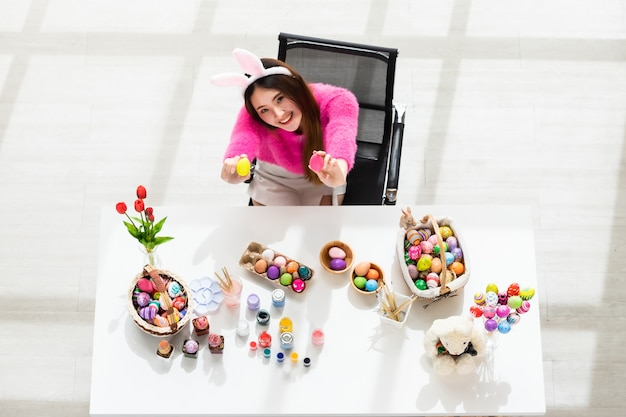 Easter holiday concept, happy asian young woman wearing bunny ears hand holding a basket with colorful easter eggs Premium Photo