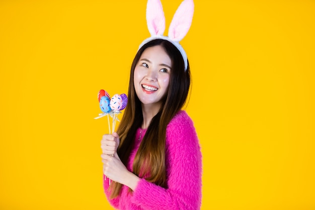 Easter holiday concept, happy smile asian young woman wearing bunny ears hand holding colorful easter eggs Premium Photo