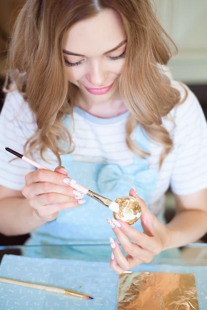 イースター休暇。ブルーエプロンを着た若い女性が卵を飾り、イースターのプレゼントを用意します。 Premium写真
