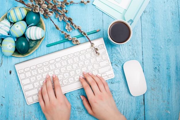 青い木製のテーブルの上のオフィスの職場でイースター。コンピューターのキーボードとコーヒーのカップの女性の手 無料写真