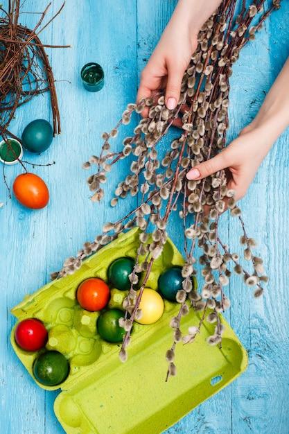 青い木製のテーブルの上のオフィスの職場でイースター。女性の手と柳の枝 無料写真