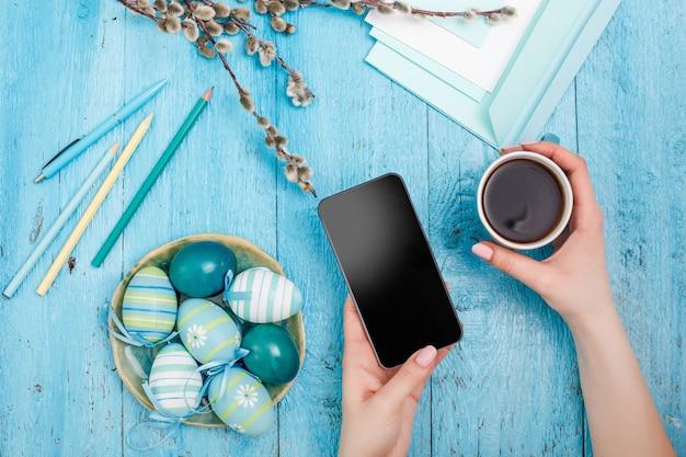 青い木製のテーブルの上のオフィスの職場でイースター。電話と一杯のコーヒーと女性の手 無料写真