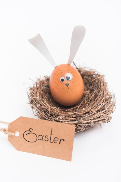 Easter inscription with egg with bunny ears in nest Free Photo