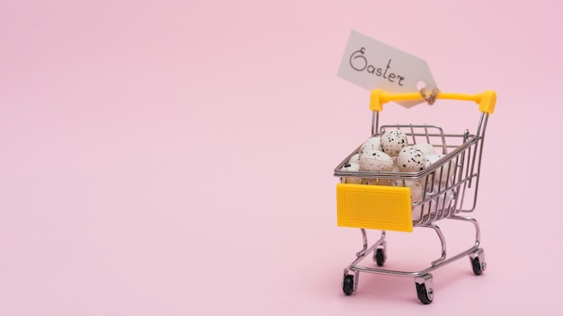 Easter inscription with eggs in small grocery cart Premium Photo