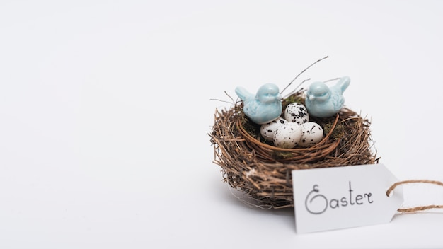 Easter inscription with quail eggs in nest on table Free Photo
