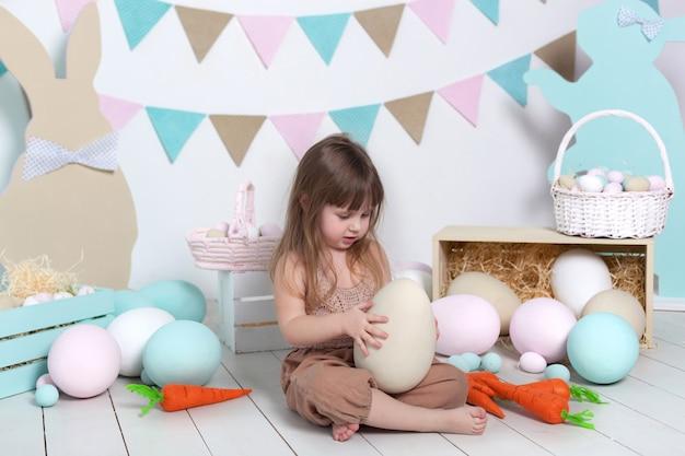 Пасхальный! маленькая девочка в комбинезоне сидит с большим пасхальным яйцом. пасхальная локация, украшения. семейные праздники, традиции. красочная комната. развитие ребенка. пасхальный декор. ребенок играет в детской Premium Фотографии