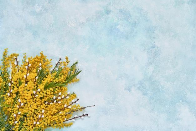 Пасхальный. цветы мимозы и пасхальное украшение на синем. копировать пространство Premium Фотографии
