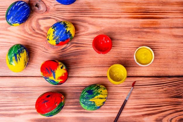 イースターマルチカラー卵、塗料、テーブルの上のブラシ。休日のための準備 Premium写真