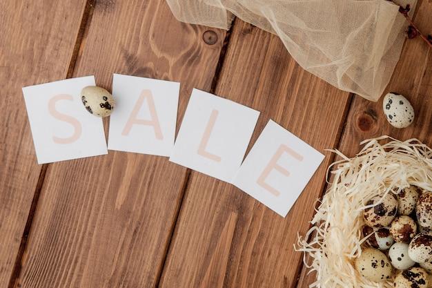 Пасхальное сообщение распродажи с пасхальными яйцами на деревянном фоне Premium Фотографии