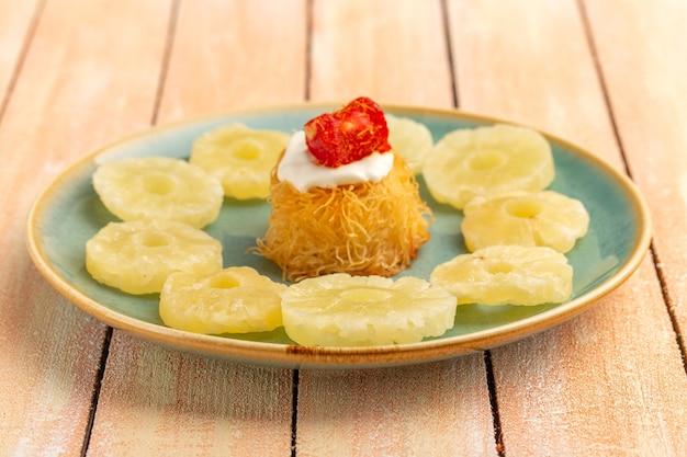 木製のテーブルに白いクリーム乾燥パイナップルリングプレート内の東洋菓子クッキー 無料写真
