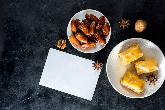 Eastern sweets with dates fruit and paper Free Photo