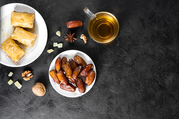 Eastern sweets with dates fruit and tea cup Free Photo
