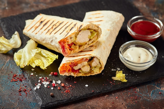 Eastern traditional shawarma with chicken and vegetables, doner kebab with sauces on slate. fast food. eastern food. Premium Photo
