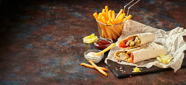 Eastern traditional shawarma with chicken and vegetables and french fries with sauces Premium Photo