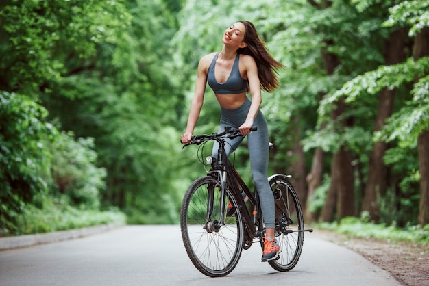 Easy wind. female cyclist on a bike on asphalt road in the forest at daytime Free Photo