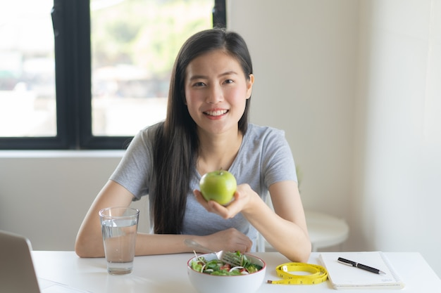 Eat healthy food on wellness lifestyle. beauty young woman holding green apple in her hand and having a salad. Premium Photo