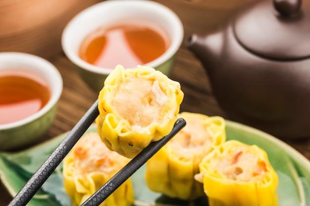 Eating dumplings with chopsticks Premium Photo