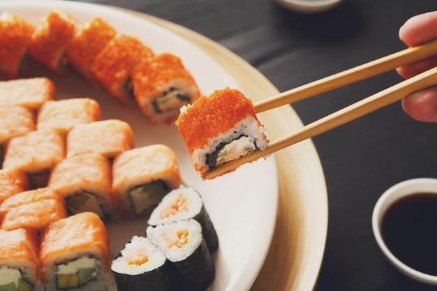 Eating sushi rolls at japanese food restaurant Premium Photo