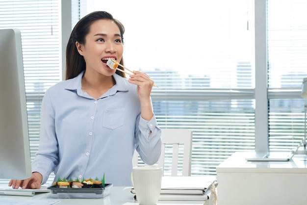 Eating sushi at workplace Free Photo