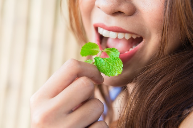 Eating vegetable herb concept: woman eat mint leaves. Premium Photo