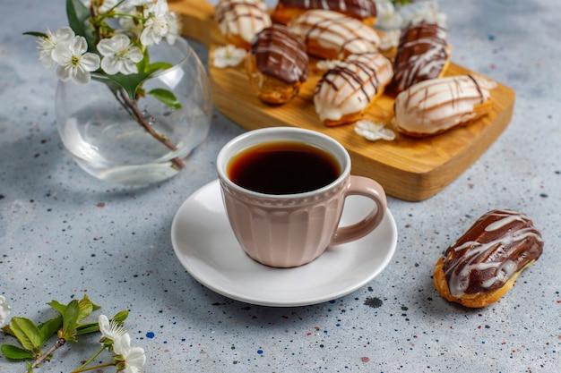 伝統的なフランスのdessert.topビューの内部にカスタードが入ったブラックチョコレートとホワイトチョコレートのエクレアまたはプロフィットロール。 無料写真