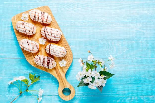 Эклеры или профитроли с черным шоколадом и белым шоколадом с заварным кремом внутри, традиционный французский десерт. Бесплатные Фотографии