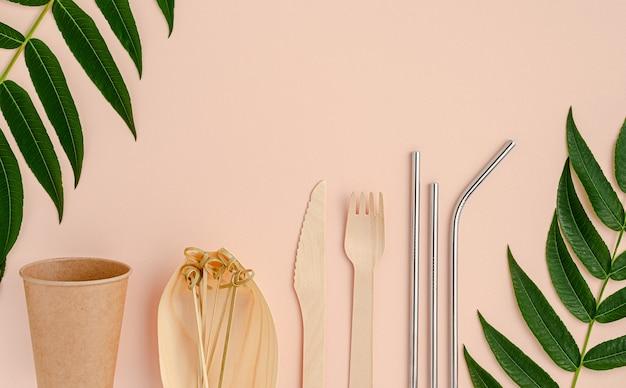 Эко столовые приборы и металлические соломинки для питья на розовом фоне Premium Фотографии