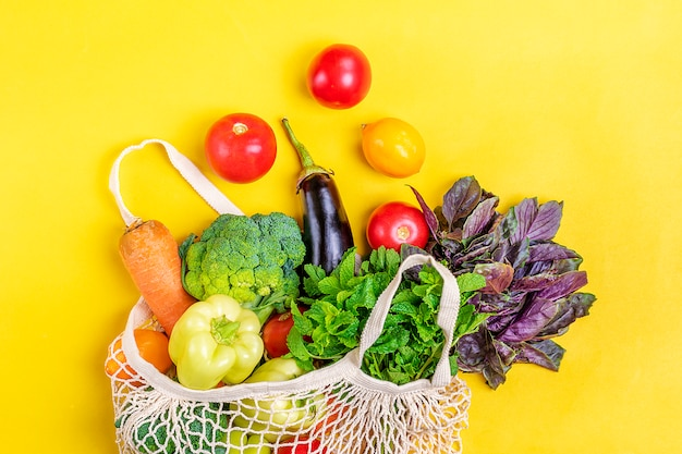 黄色の有機野菜とエコメッシュショップバッグ。フラット横たわっていた、トップビュー。 Premium写真