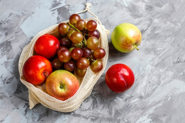 Eco-friendly simple beige cotton shopping bags for buying fruit and vegetables with summer fruits. Free Photo