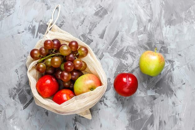 夏の果物と一緒に果物や野菜を買うための環境に優しいシンプルなベージュの綿の買い物袋。 無料写真