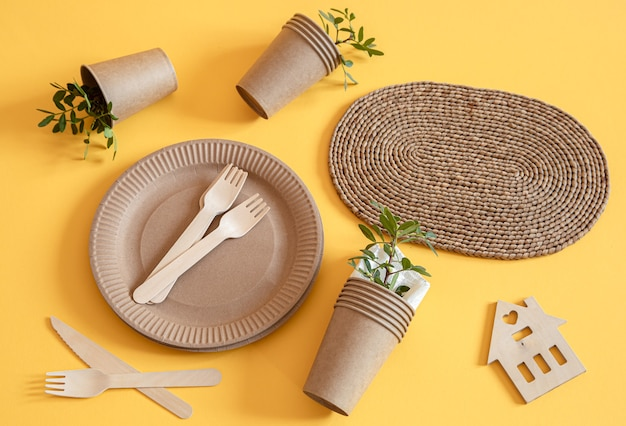 Eco-friendly, stylish recyclable paper tableware. paper food boxes, plates, and cornstarch cutlery on a trending orange background. Free Photo