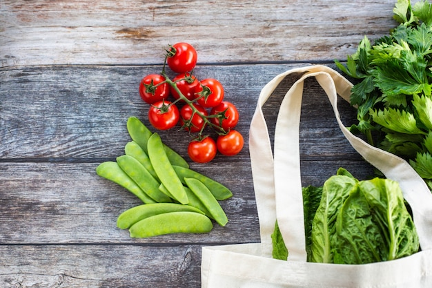 Eco shopping bag with fresh organic vegetables and salad on wooden background, flat lay Premium Photo