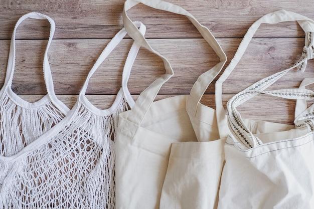 Сумка хозяйственная сумка хлопка tote eco на деревянной предпосылке. устойчивость и многократное использование источника для сохранения окружающей среды. Premium Фотографии